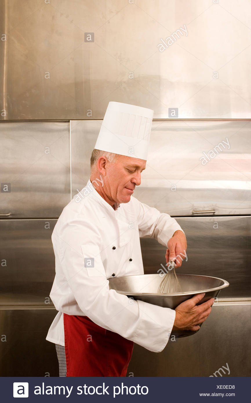 Mature male chef whisking ingredients in large bowl in commercial kitchen side view - Stock Image