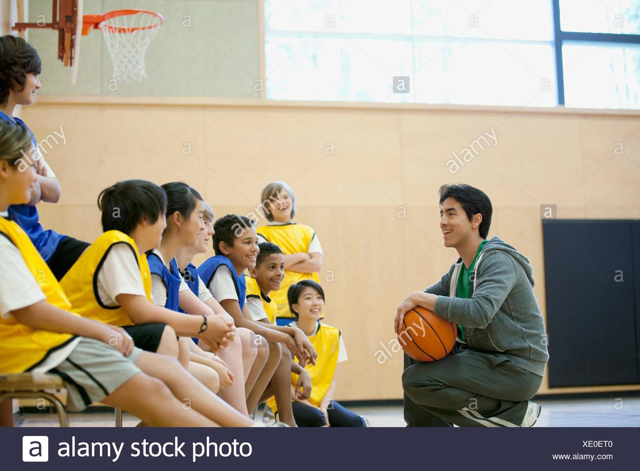 teacher instructing students on basketball - Stock Image