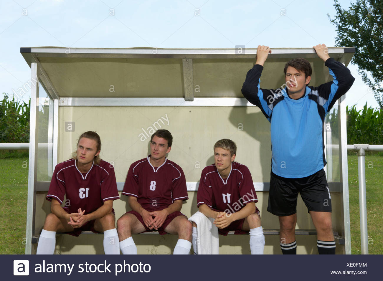 Strained kickers sitting on substitutes' bench - Stock Image