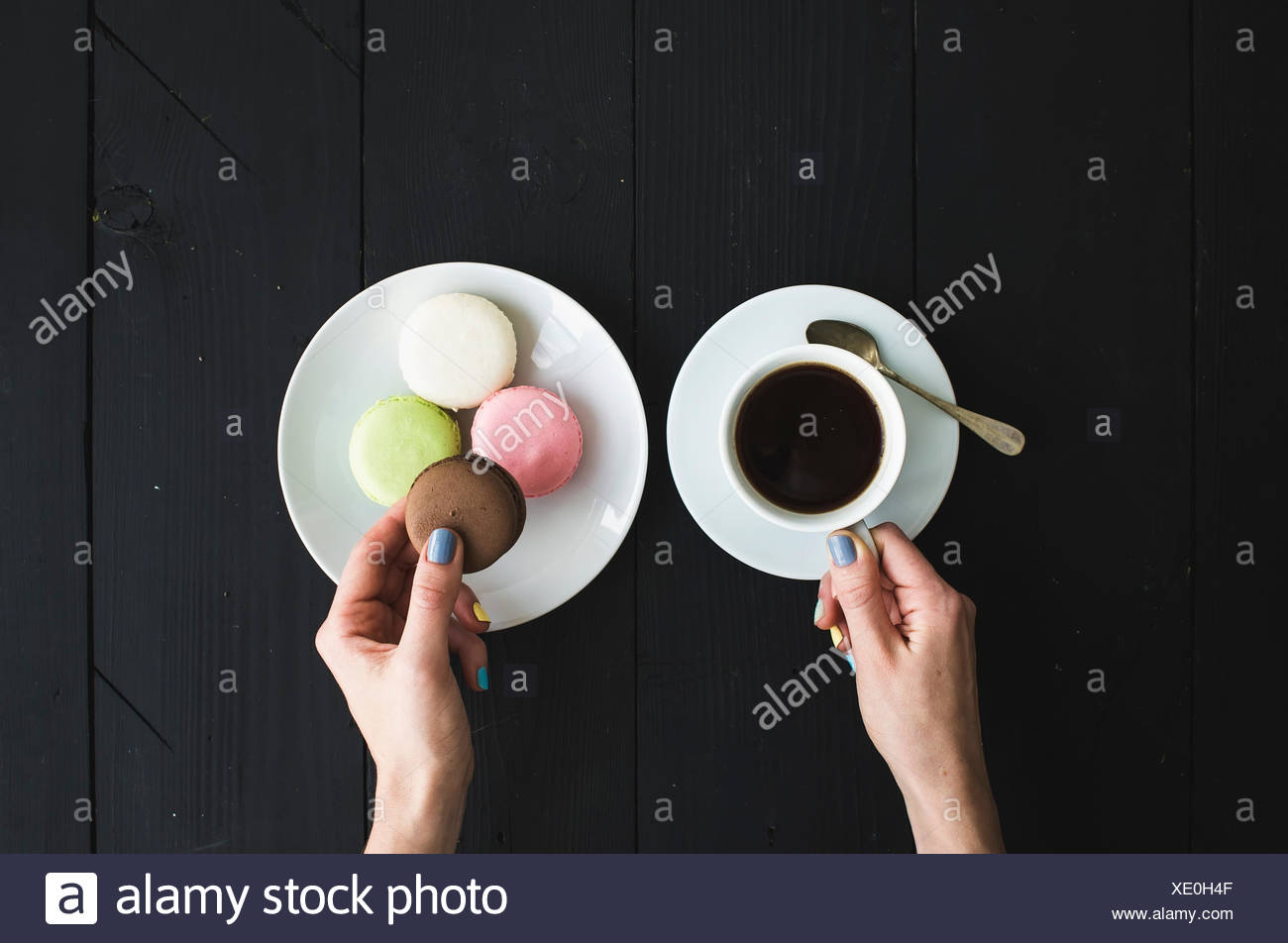 Macaron cookies, cup of espresso and ladie's hands over black wooden backdrop . Top view - Stock Image