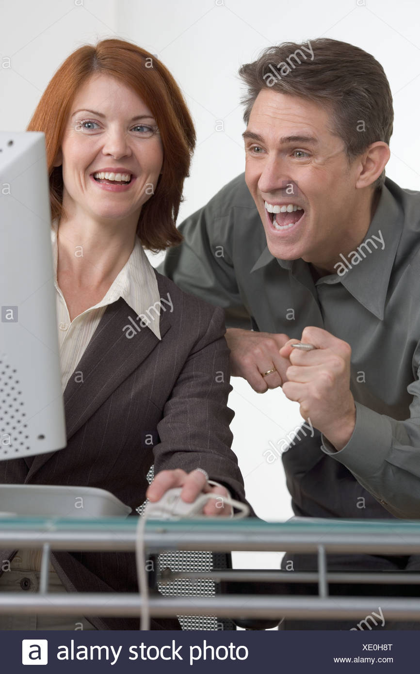 Excited business people at computer - Stock Image