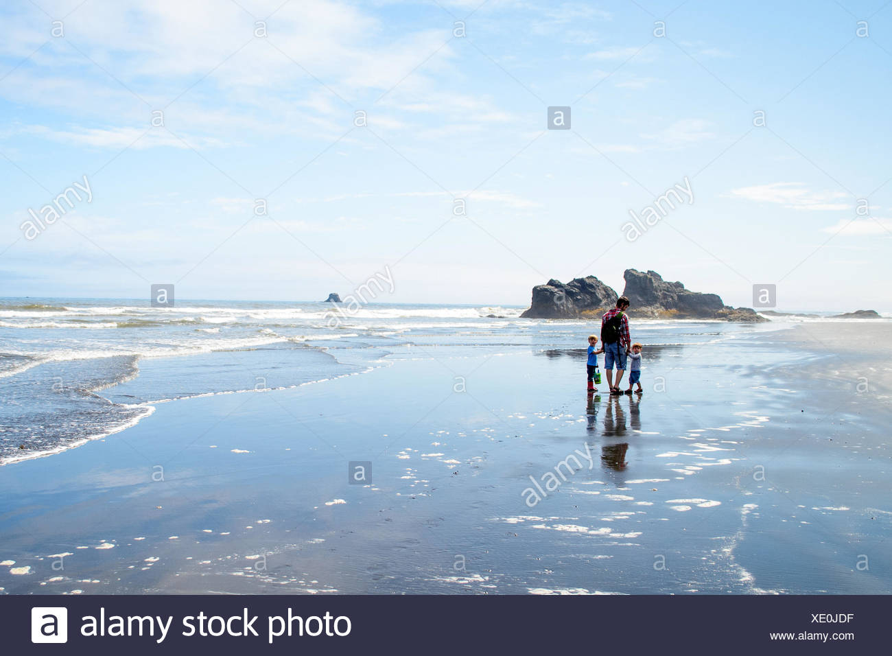 Mother with two children( 2-3, 4-5) standing at beach - Stock Image