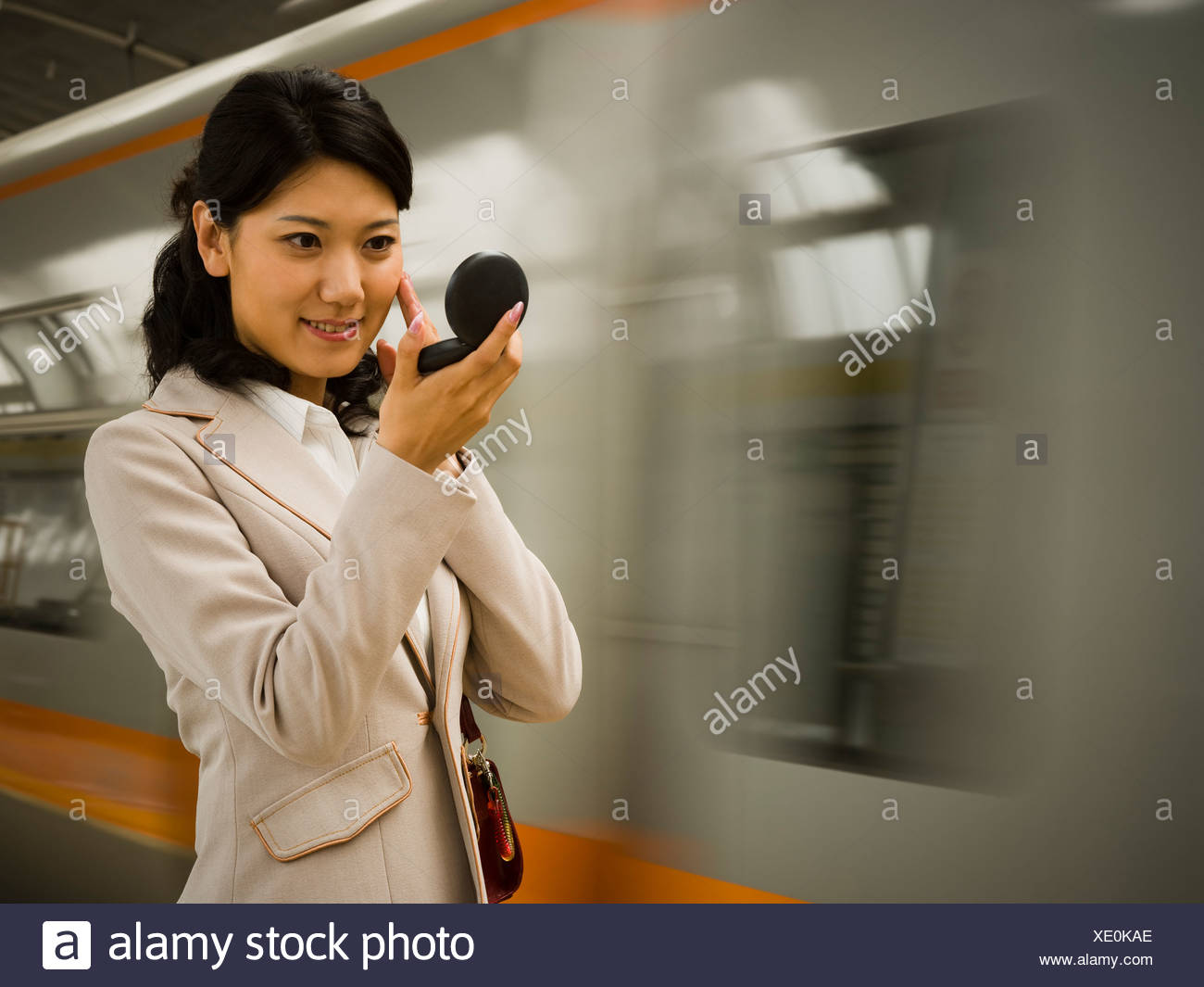 Businesswoman on subway platform smiling and looking in compact mirror - Stock Image