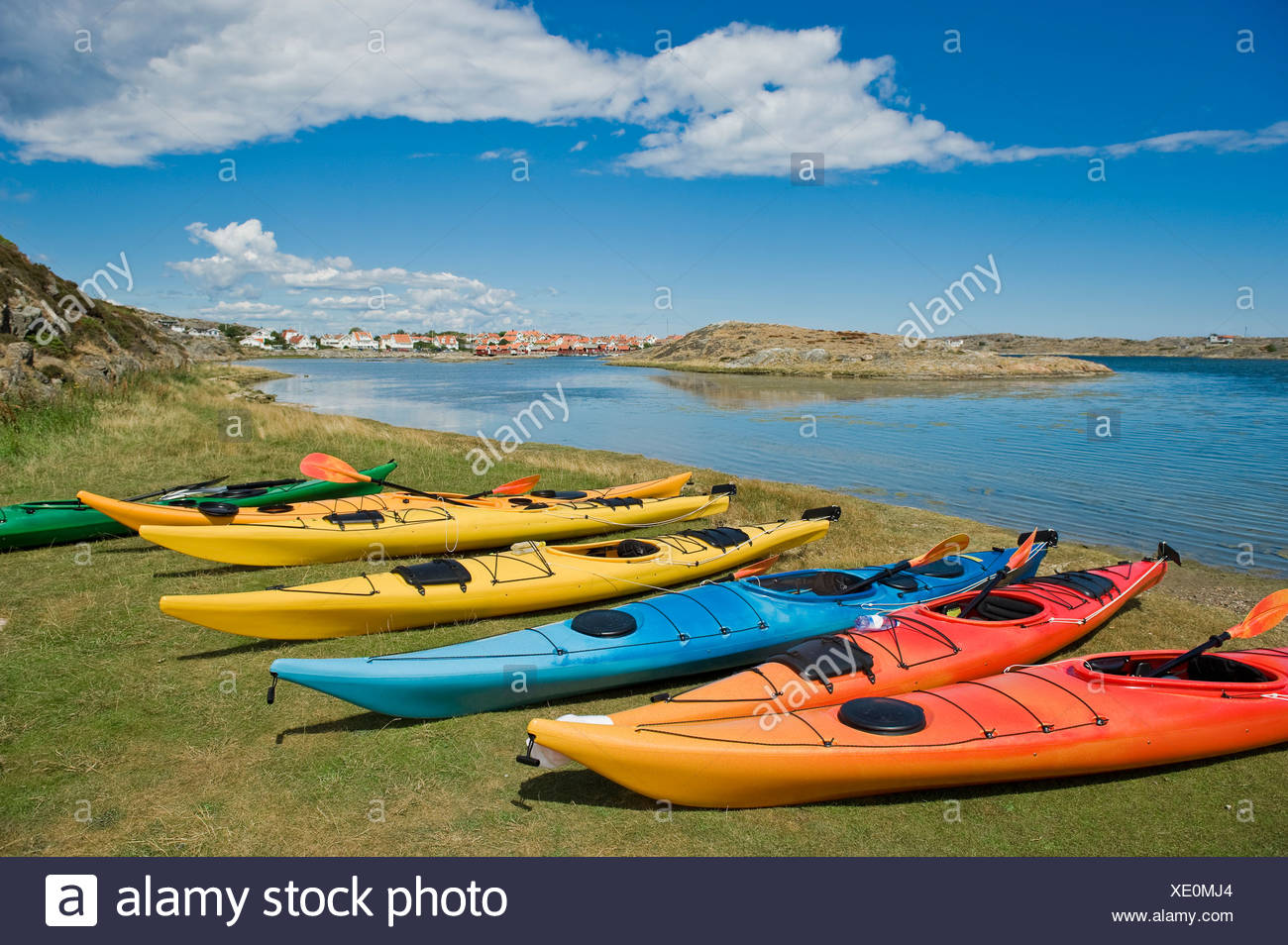 Several kayaks on grass by the calm sea below clouds in the sky Stock Photo