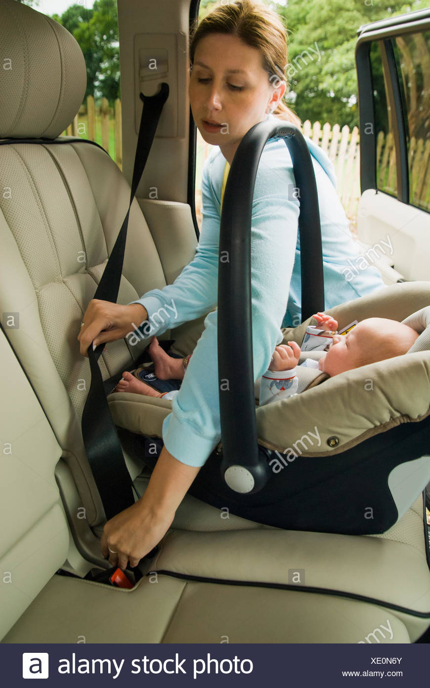 Mother strapping baby son in back seat of a car Stock Photo