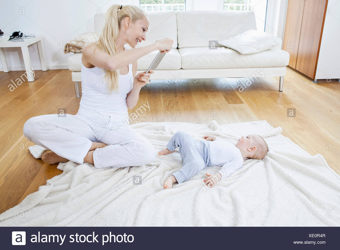 Mother photographing baby boy with digital tablet - Stock Image