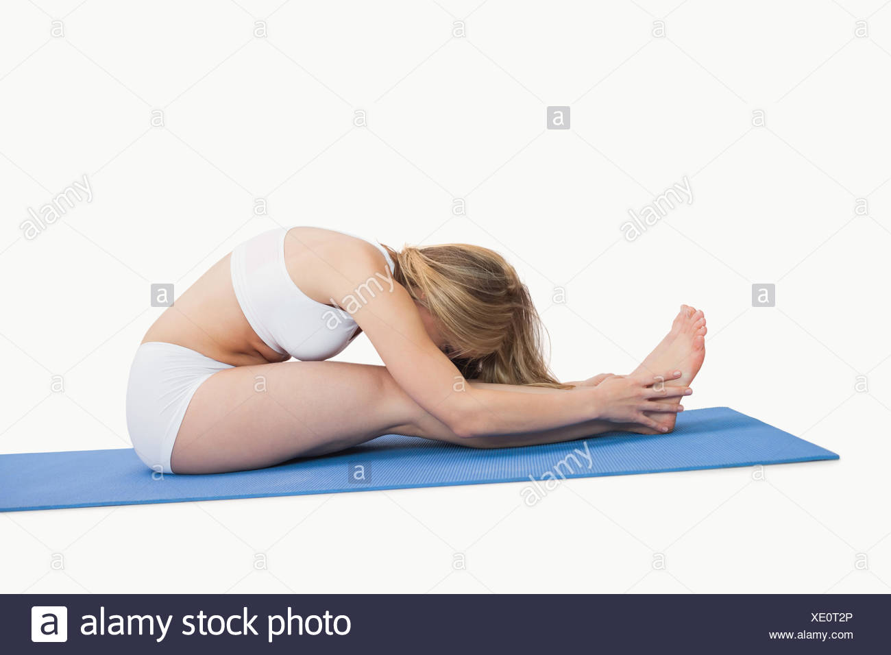 Side view of young woman doing the paschimottanasana pose over white background - Stock Image