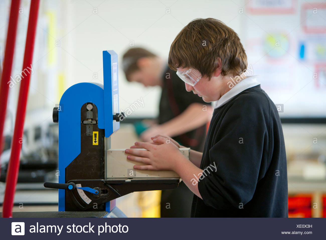 Boy with goggles using woodworking machinery in classroom - Stock Image