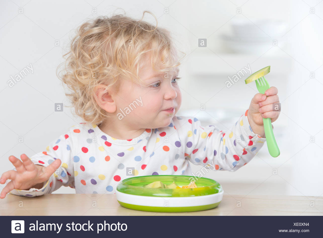 Curious baby eating avocado with fork - Stock Image