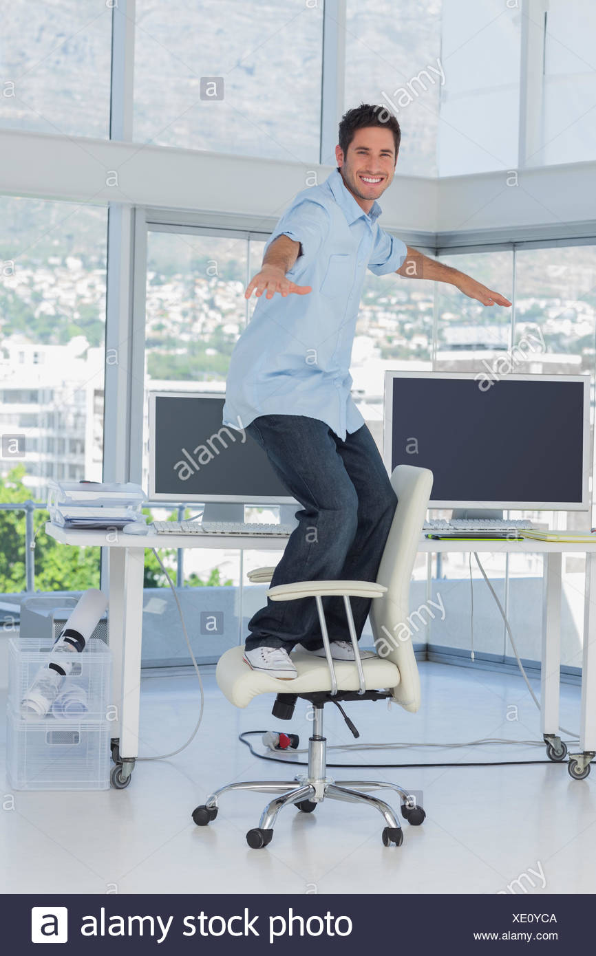 Creative designer surfing his swivel chair - Stock Image