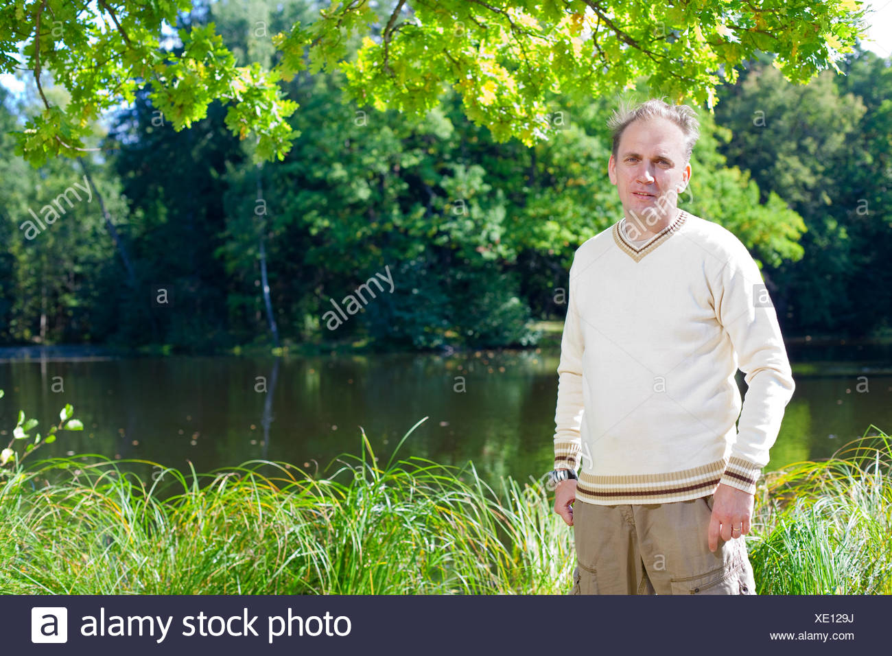 The man in a beige jumper on the bank of a pond - Stock Image