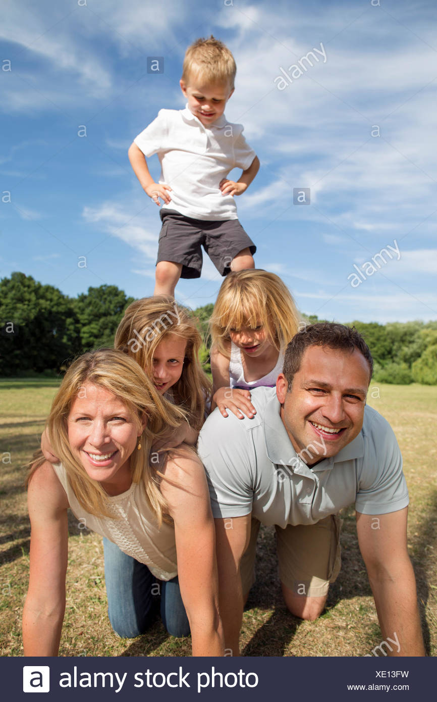 Family with three children playing in a park. - Stock Image