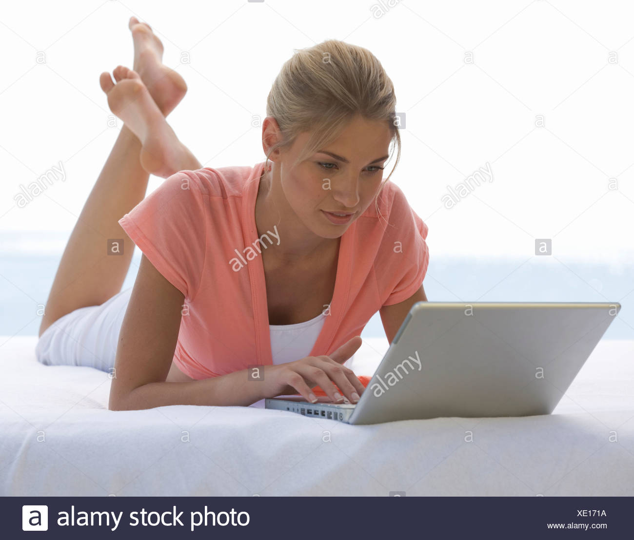 A young woman working on a laptop - Stock Image