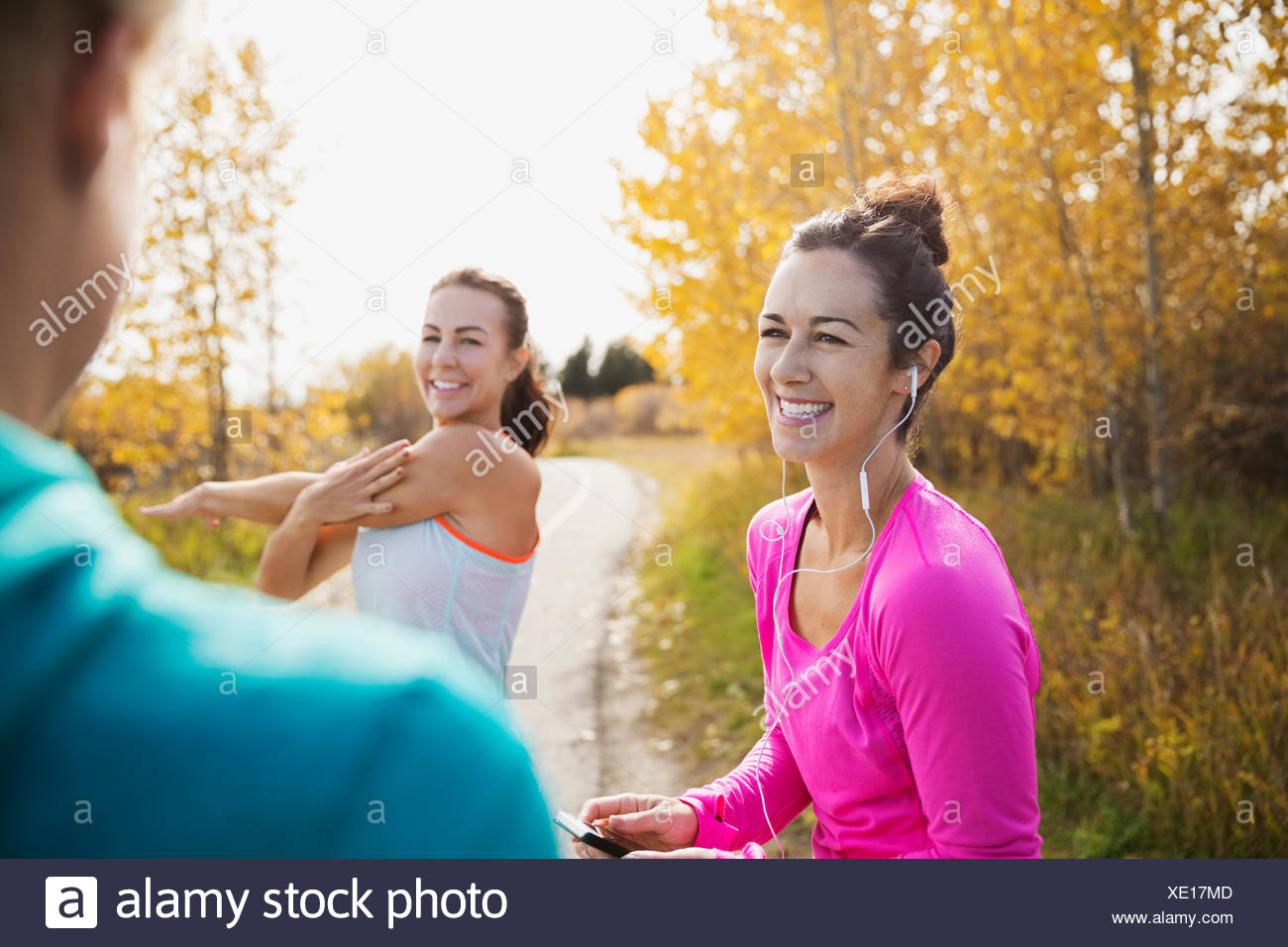 Joggers stretching and talking on autumn path - Stock Image