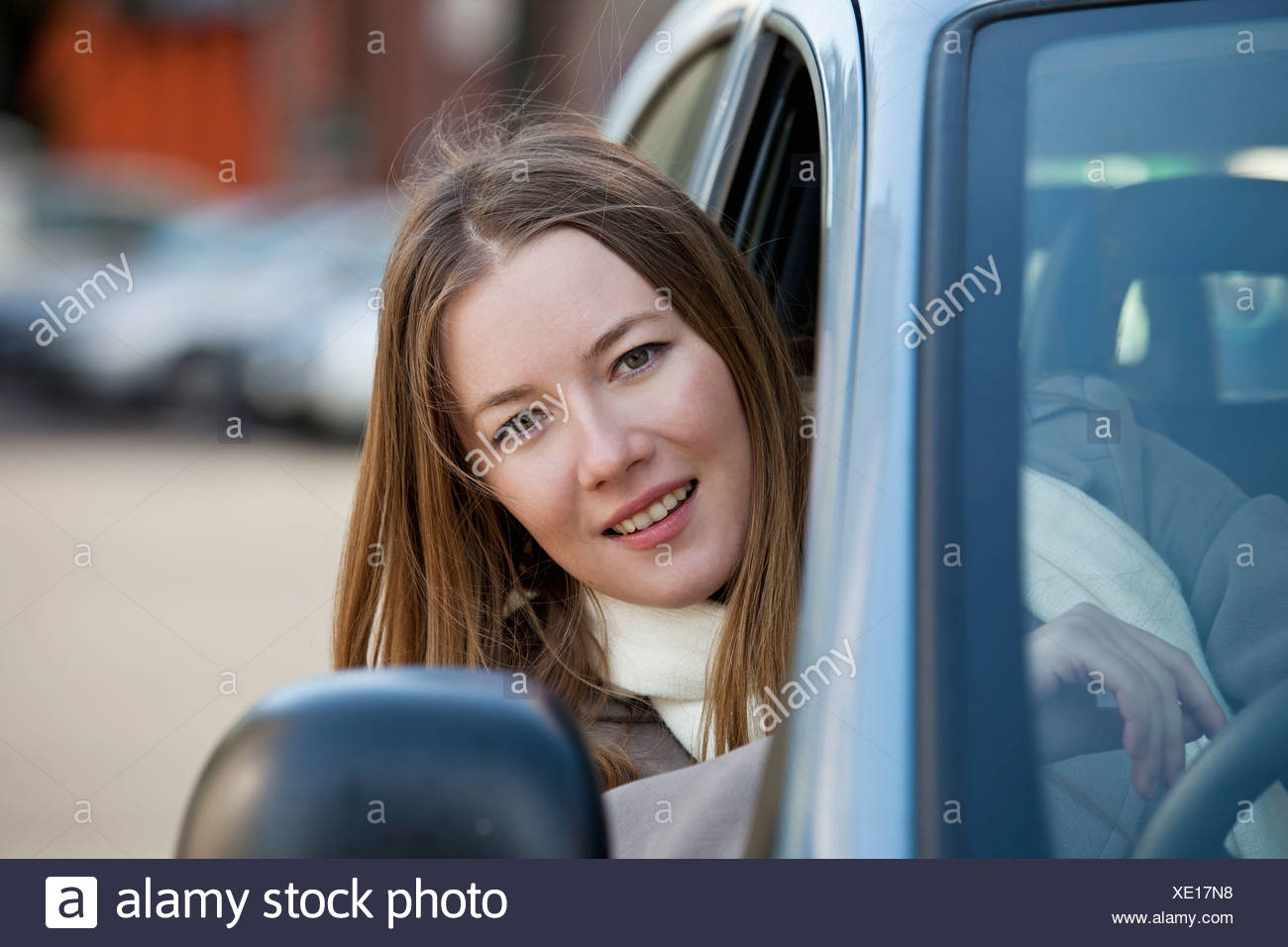 Woman driver with head out of window - Stock Image