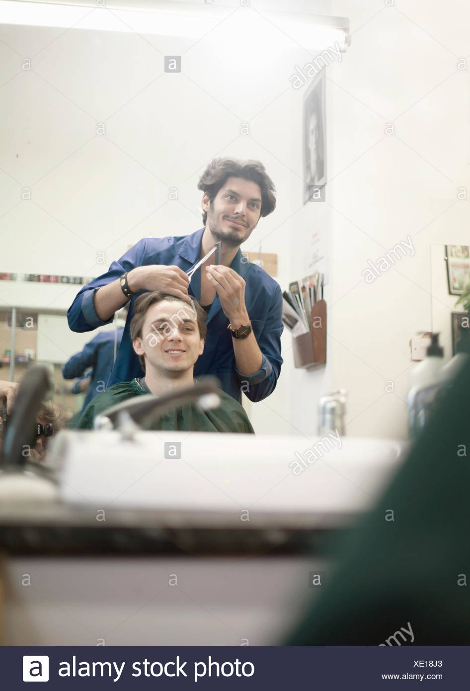Barber styling customer's hair - Stock Image