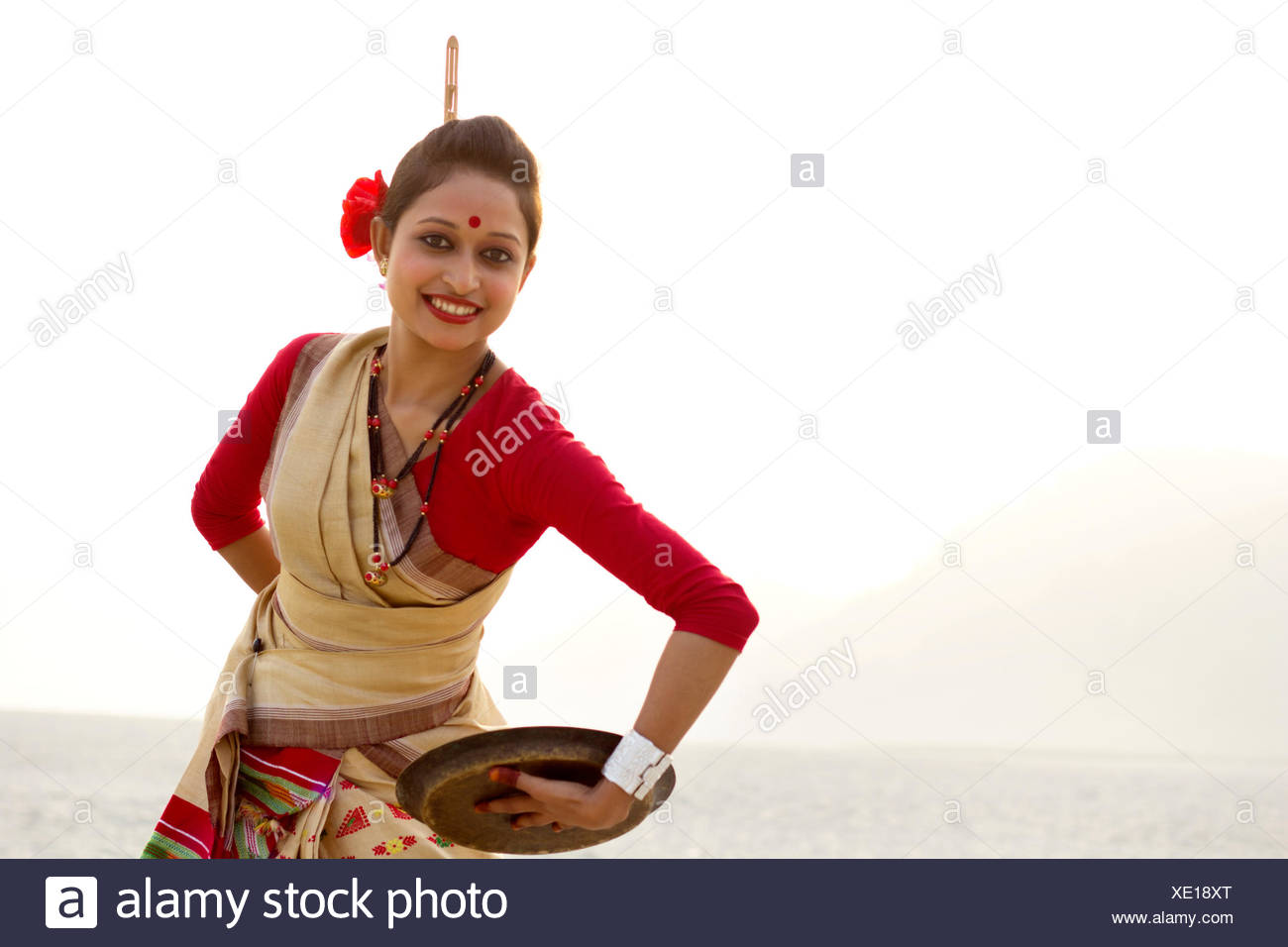 Portrait of Bihu woman dancing with brass plate - Stock Image