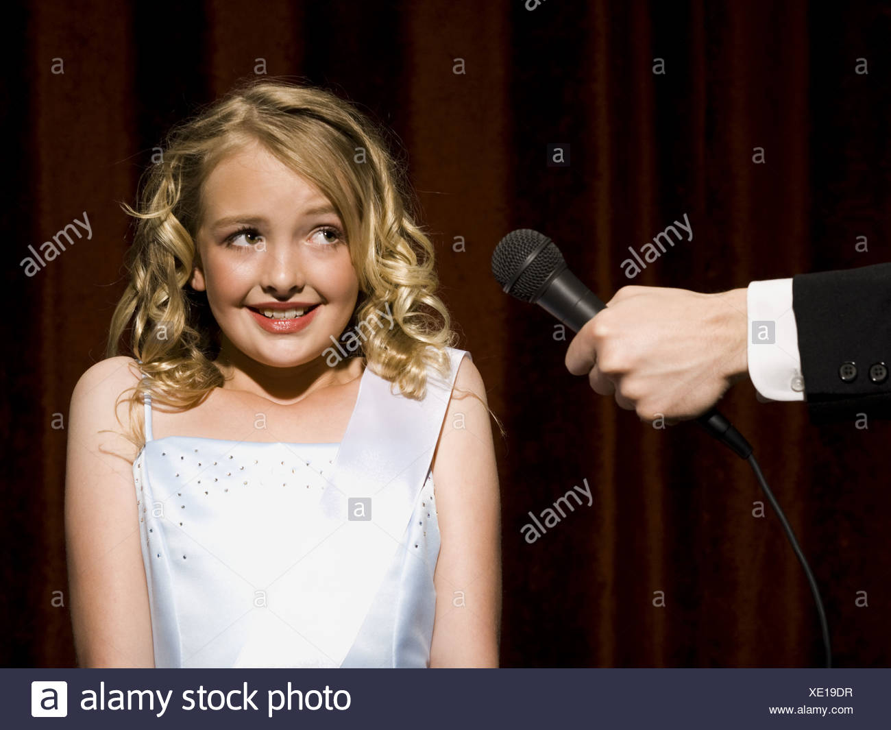 Girl beauty pageant contestant with microphone looking nervous - Stock Image