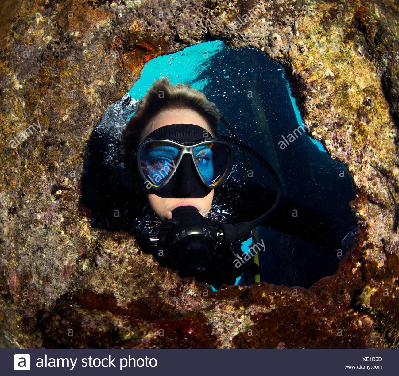 Diver peers through porthole. - Stock Image