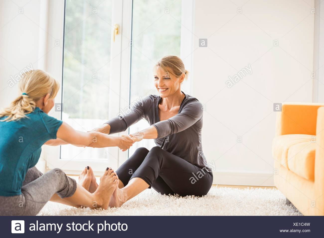 Two mature women exercising together on living room floor - Stock Image