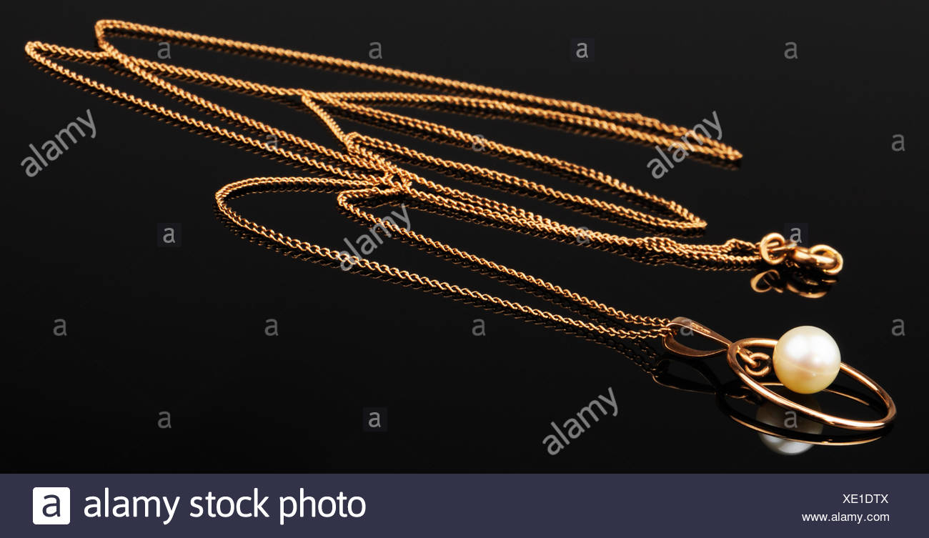 Golden chain with pendant on black mirrored surface Stock Photo
