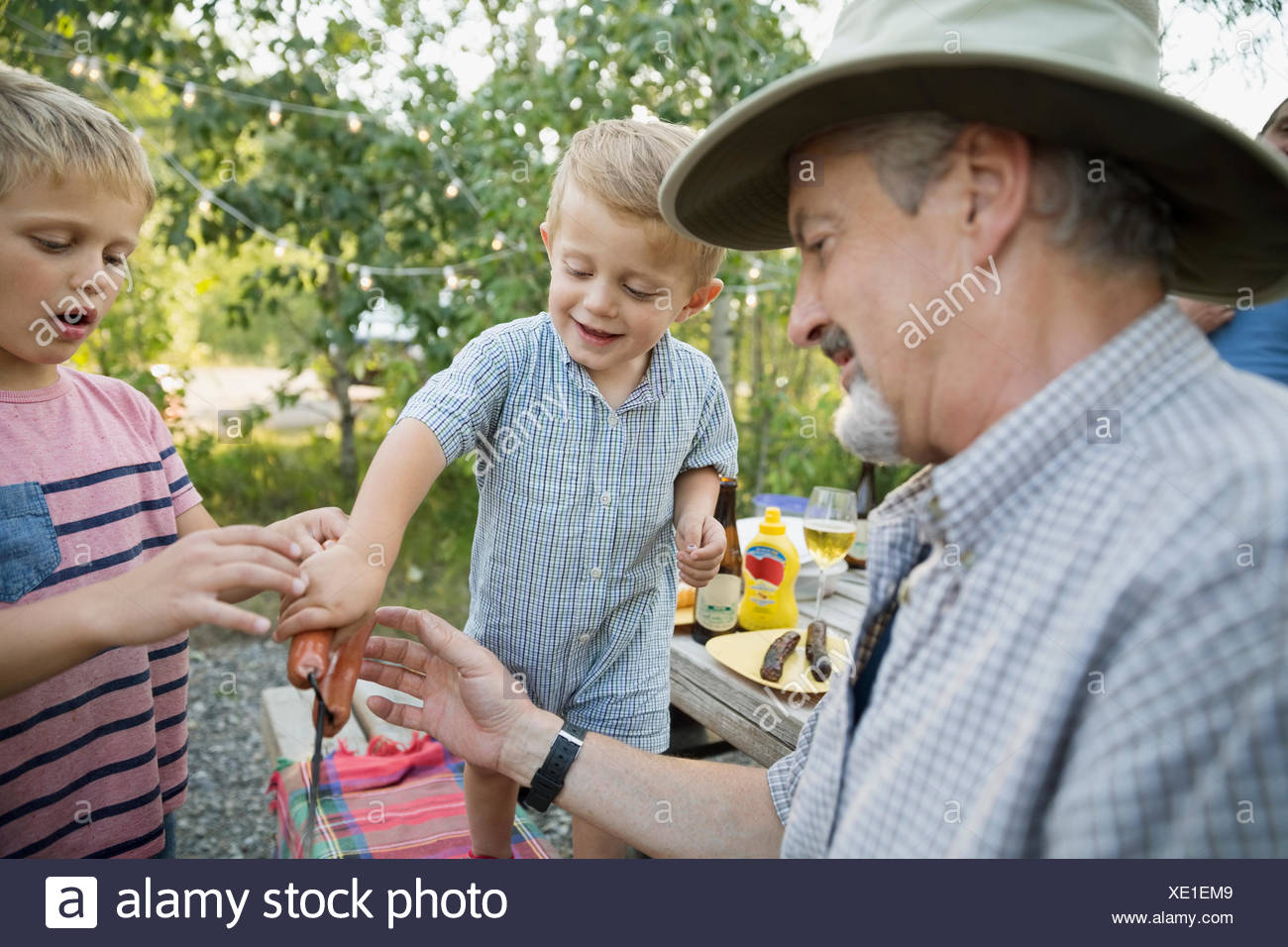 Close up grandfather and grandsons barbecuing hot dogs - Stock Image