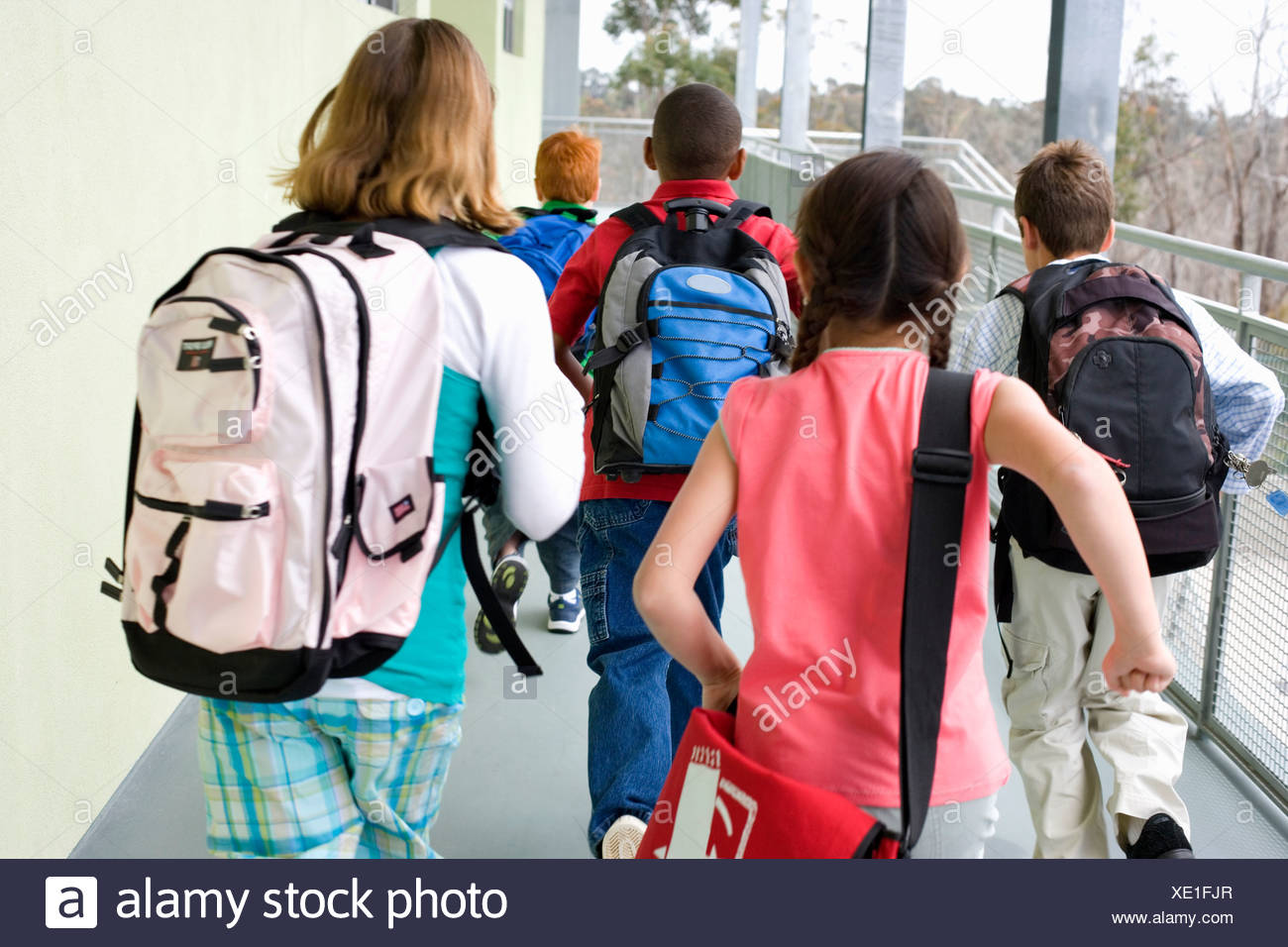 School children 10-12 with rucksacks, rear view - Stock Image