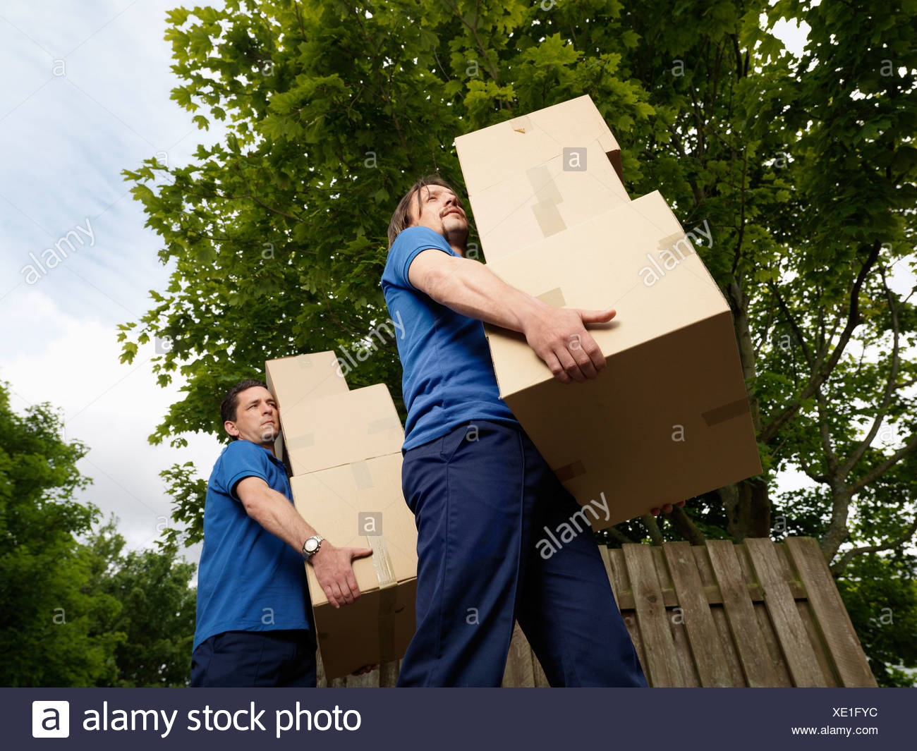 two men carrying boxes - Stock Image