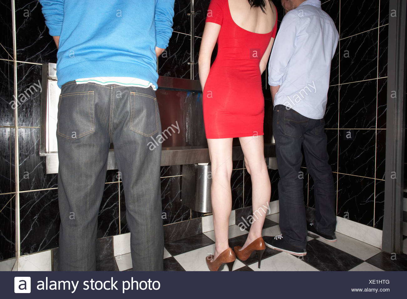 Woman and two men standing at mens urinal - Stock Image