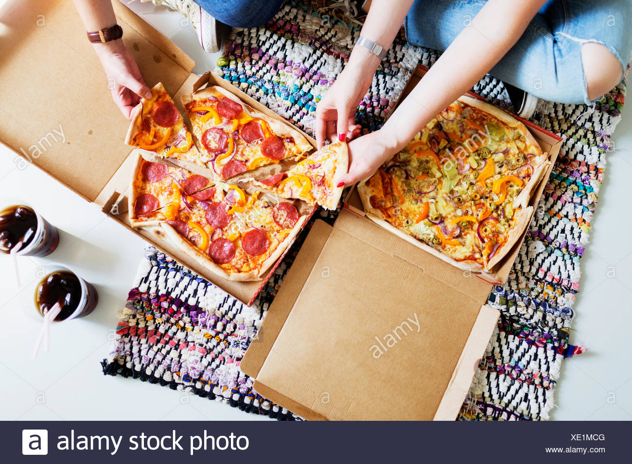 High angle view of friends eating pizza with cola in new home - Stock Image