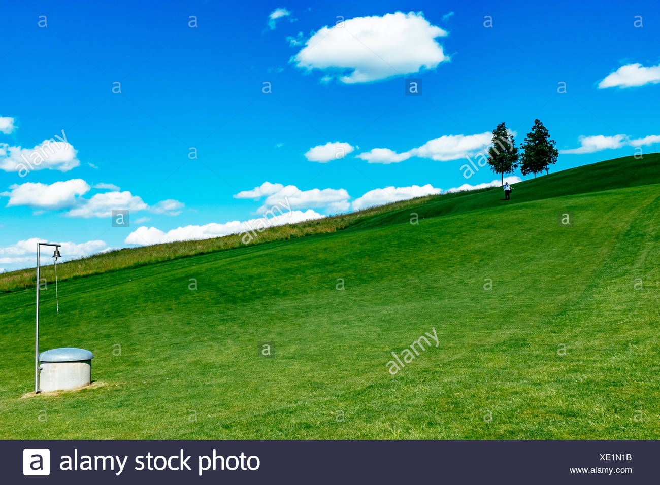 Scenic View Of Green Hill Against Cloudy Blue Sky - Stock Image
