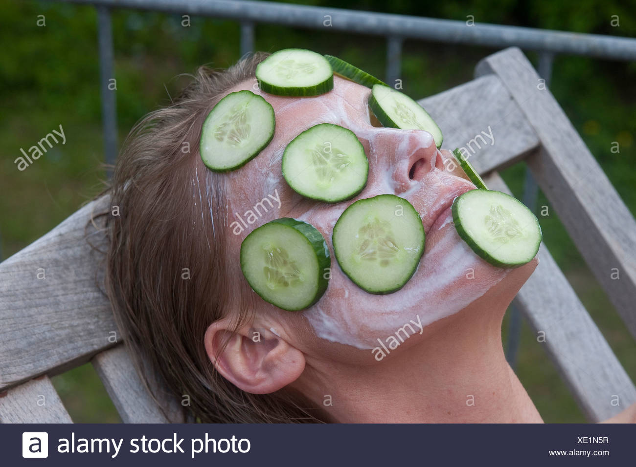 woman lying in a canvas chair with a cucumber mask - Stock Image