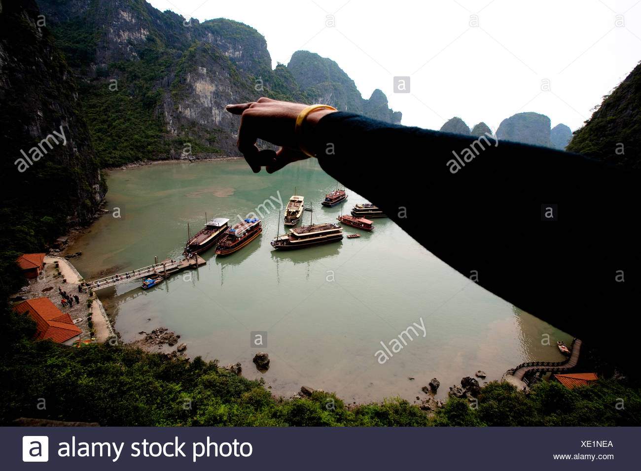 A climber points to limestone cliffs in Halong Bay, Vietnam.  Halong Bay has thousands of climbable limestone formations through - Stock Image
