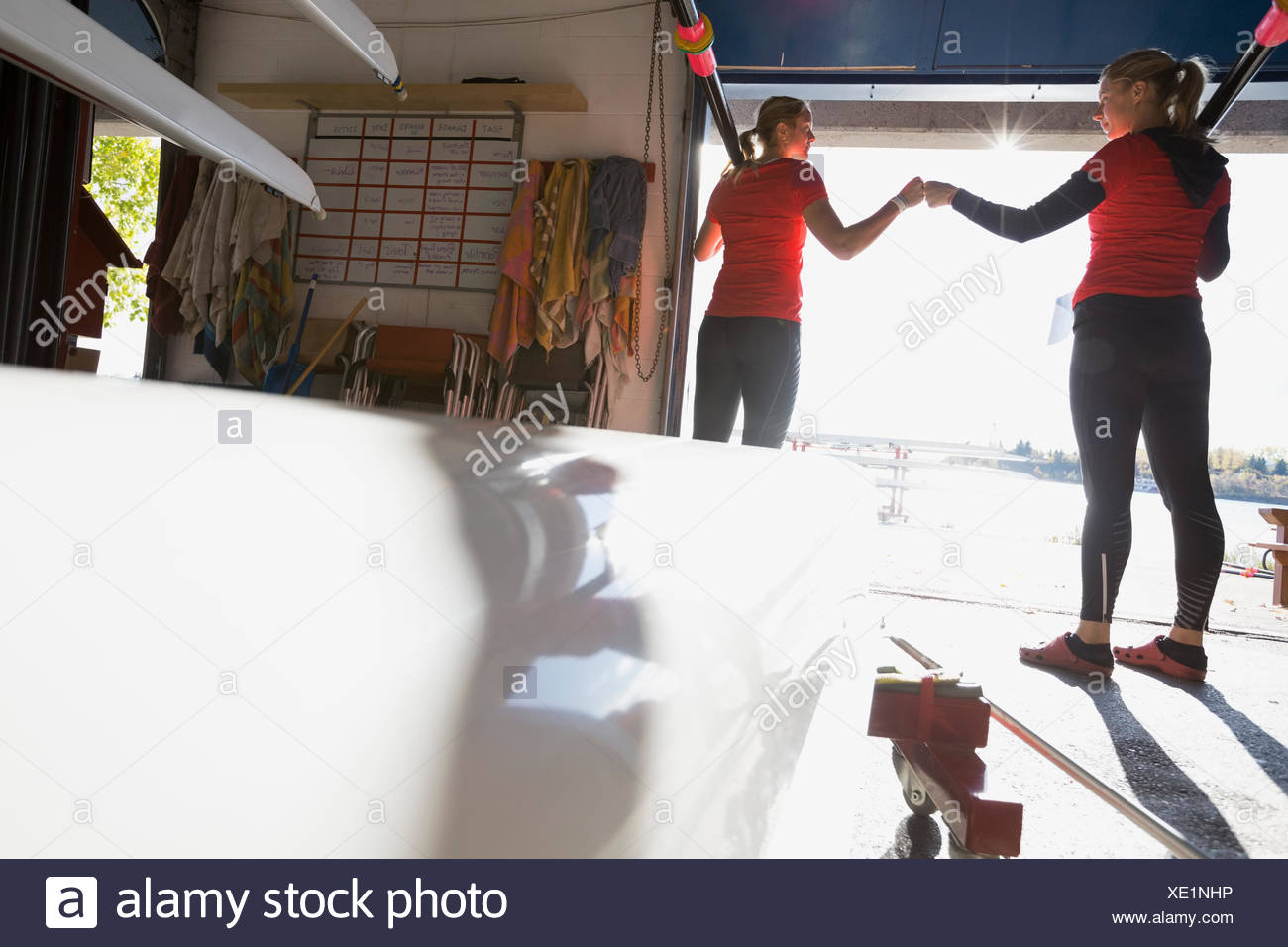 Rowers fist pumping in boathouse - Stock Image