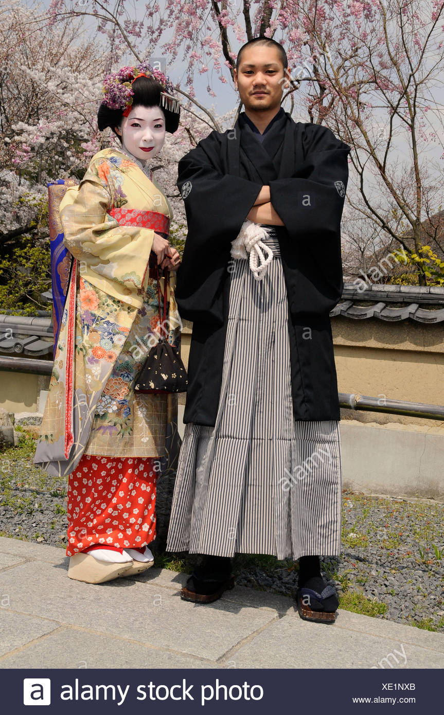 A Maiko, a trainee Geisha, and Japanese man wearing a Kimono, in front of cherry trees in bloom, Kyoto, Japan, Asia Stock Photo