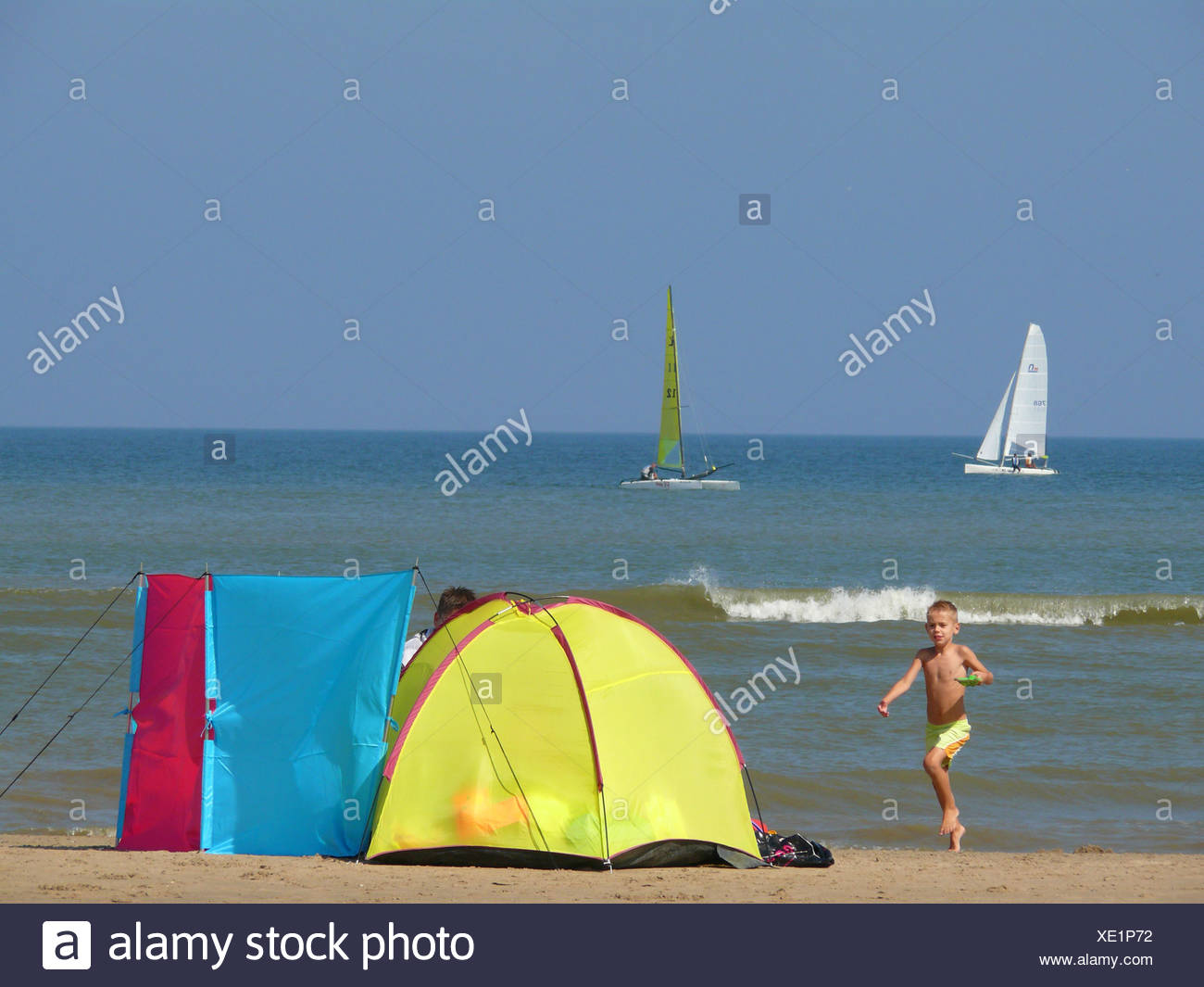tourist family lying at the beach with windbreak, Netherlands, North Sea, Noordwijk - Stock Image