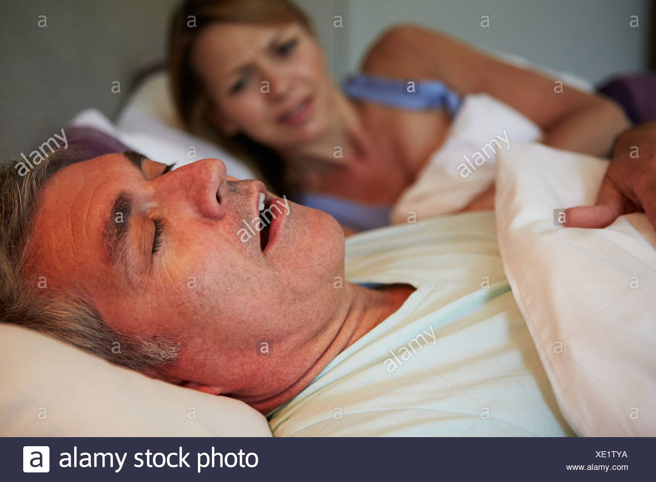 Man Keeping Woman Awake In Bed With Snoring - Stock Image
