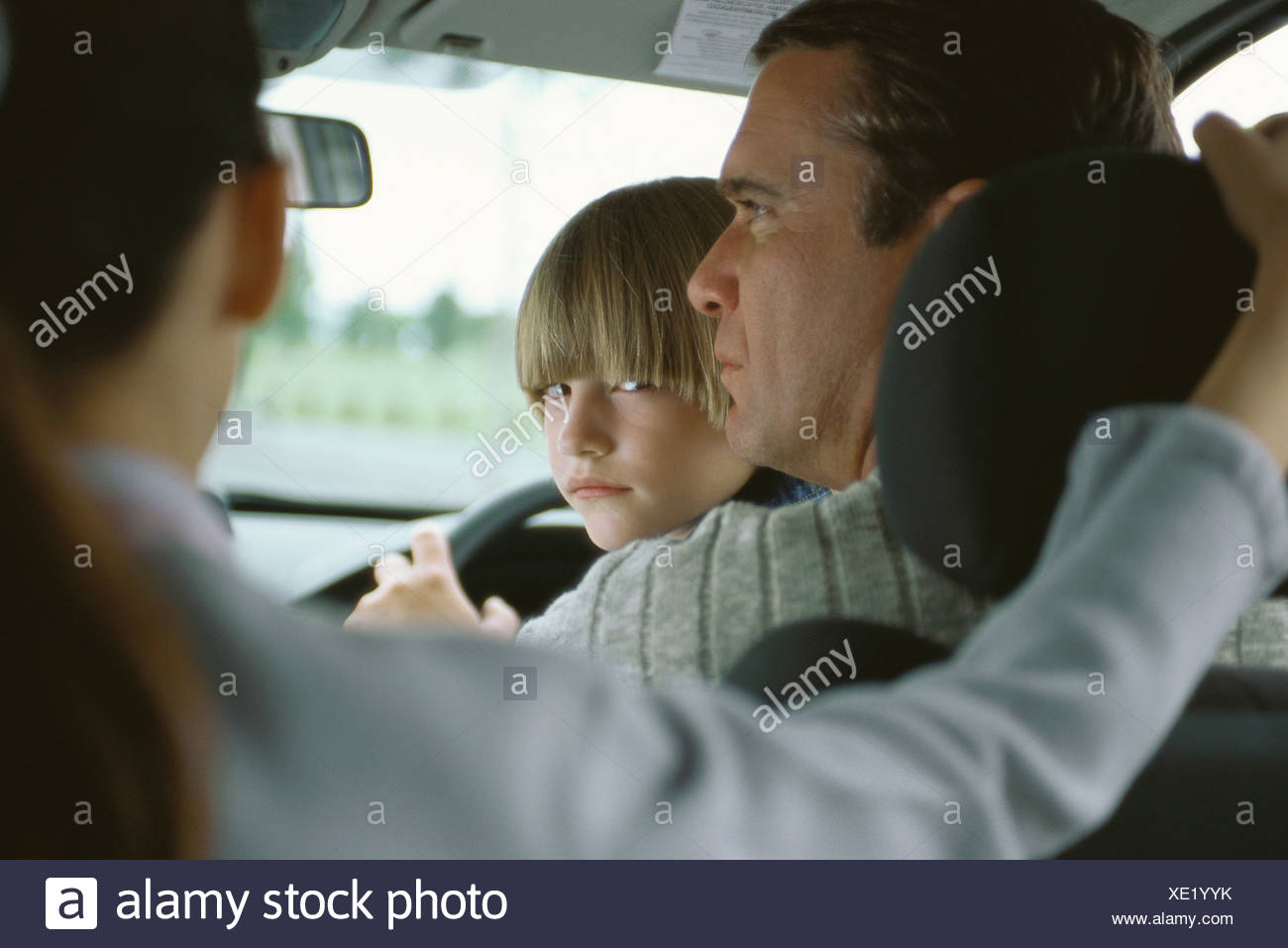 Boy sitting in father's lap in car, looking over shoulder at sister in back seat Stock Photo