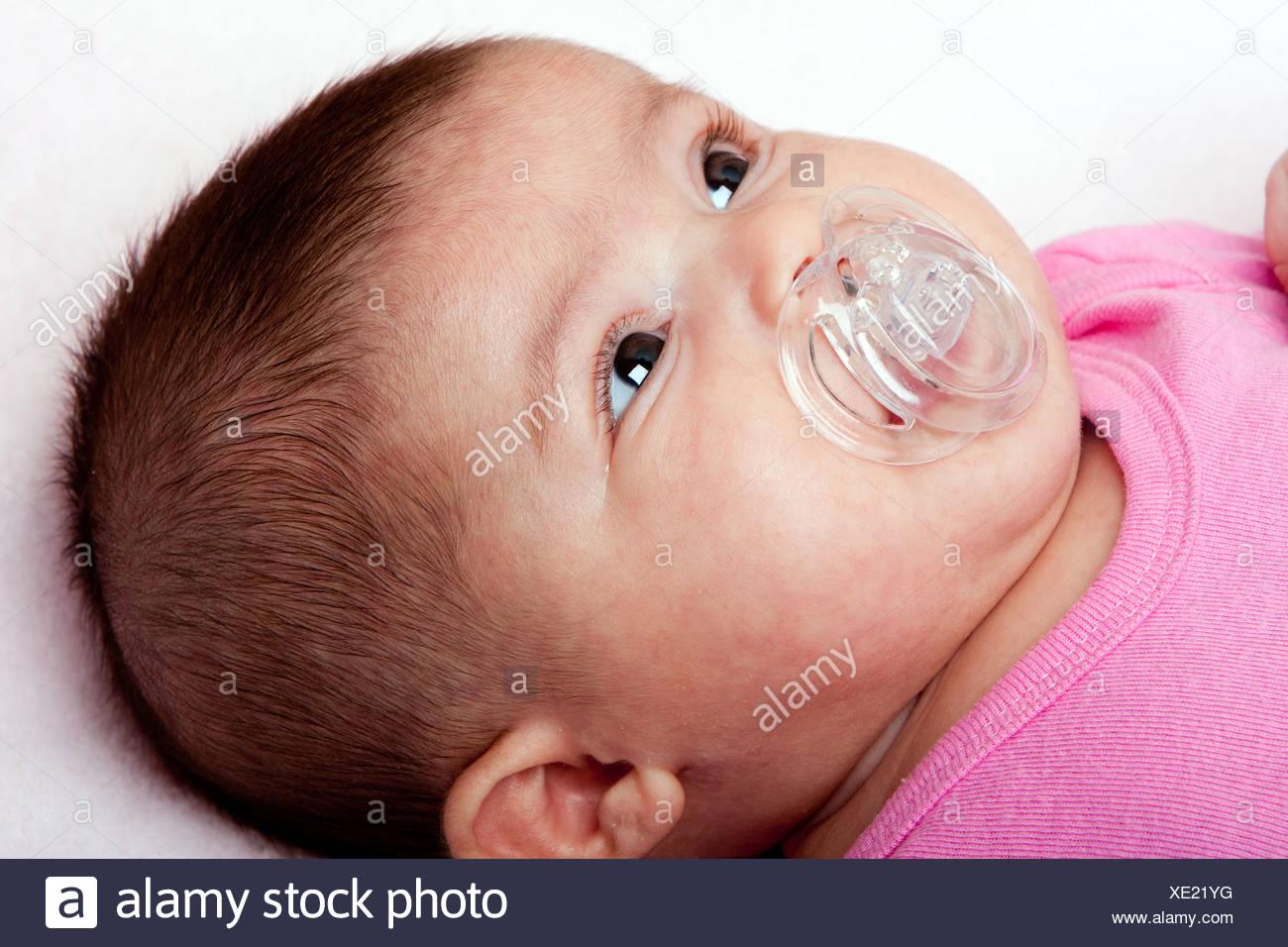 Beautiful caucasian hispanic latina baby infant girl with plastic pacifier cute face of a newborn