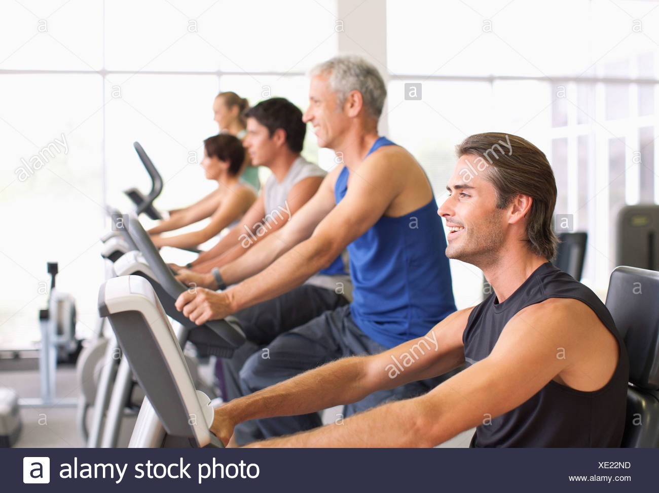 People working out on exercise machines in gymnasium Stock Photo