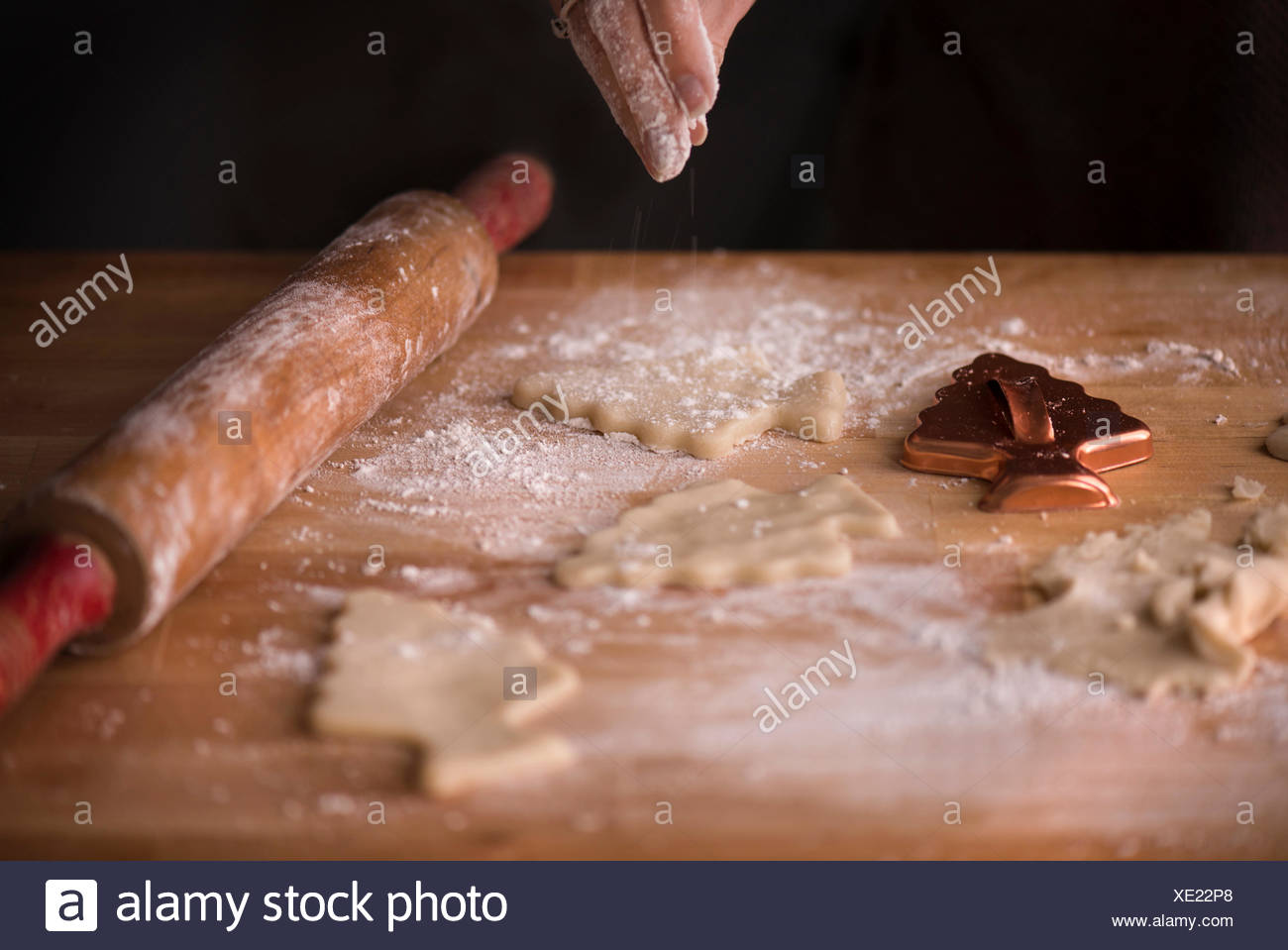 Woman sprinkling flour over sugar cookie dough cut into Christmas tree shapes. Antique rolling pin and cookie cutter on a butche - Stock Image