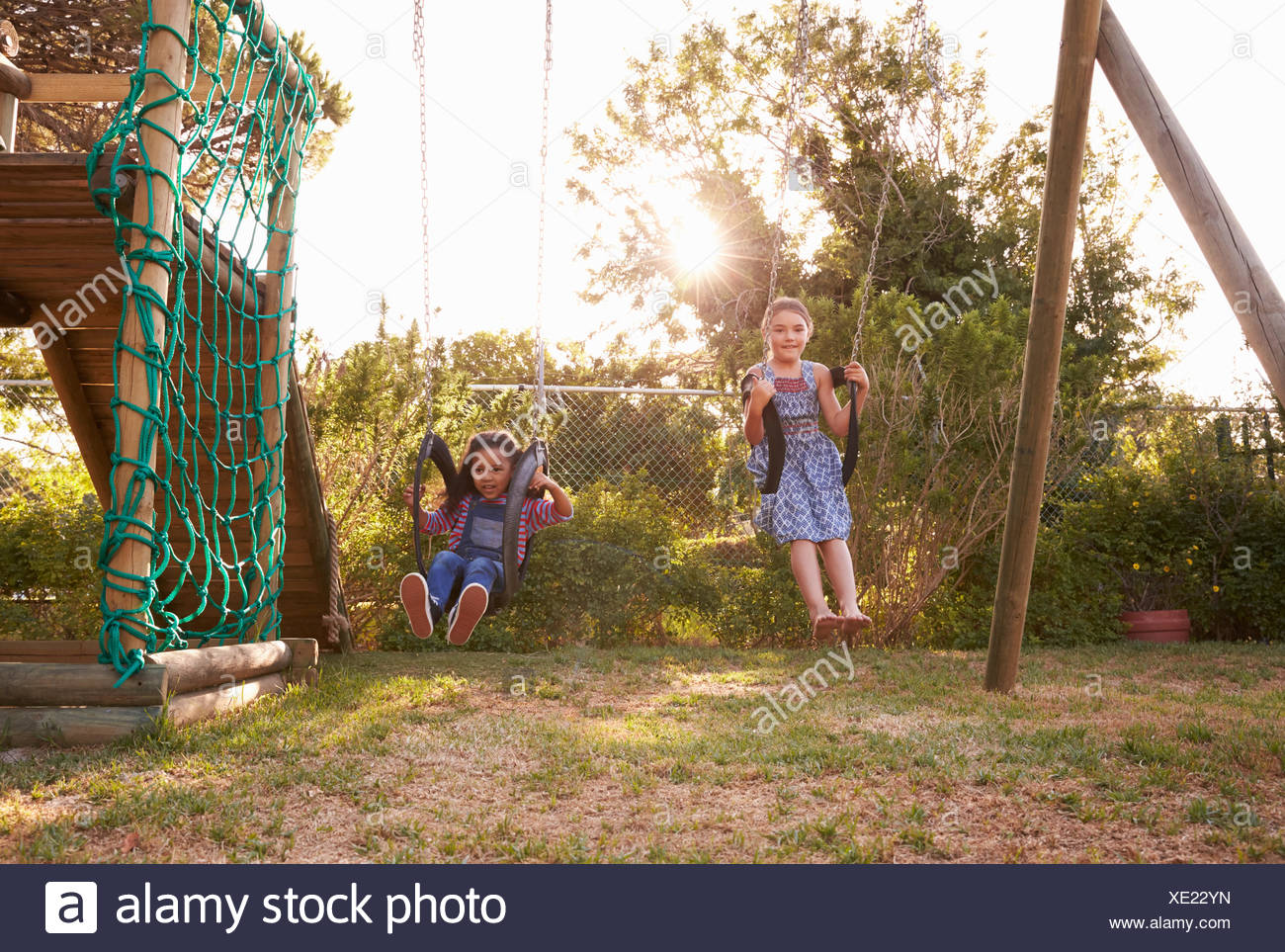 Two Girls Playing Outdoors At Home On Garden Swings Stock Photo ...