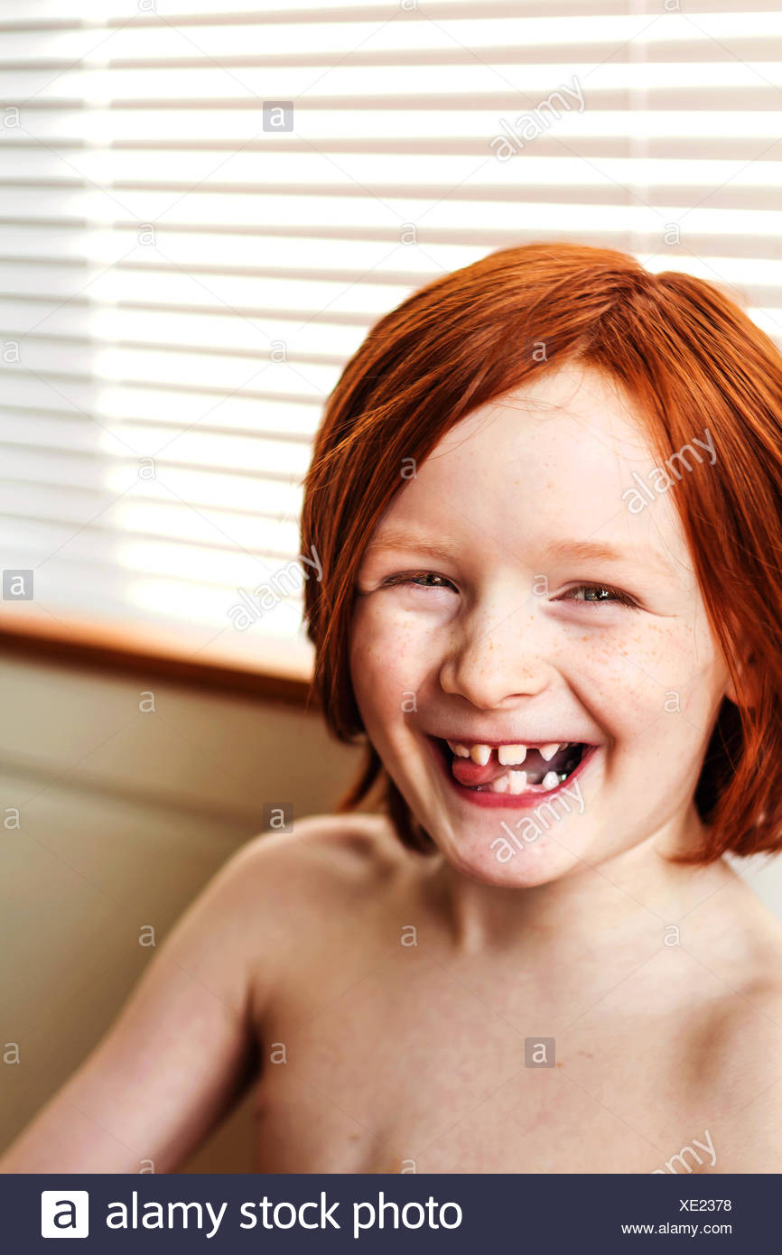 Portrait of smiling redhead boy - Stock Image