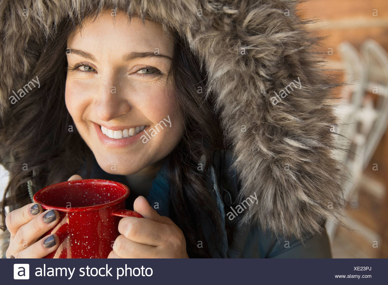 Portrait of woman in fur hood drinking coffee outdoors - Stock Image