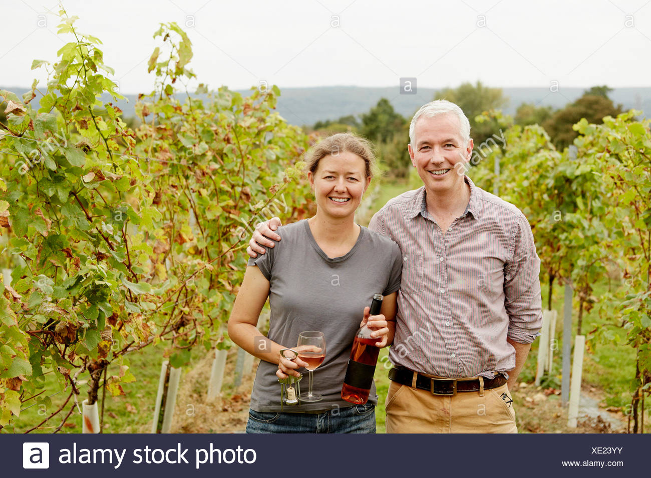 A couple, vineyard founder and her partner standing among the rows of vines. - Stock Image