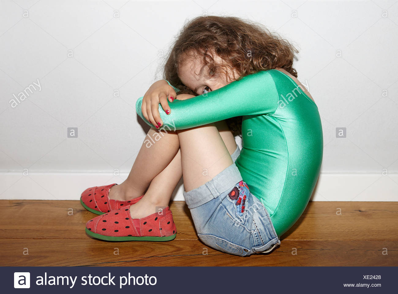Child on floor in fetal position - Stock Image