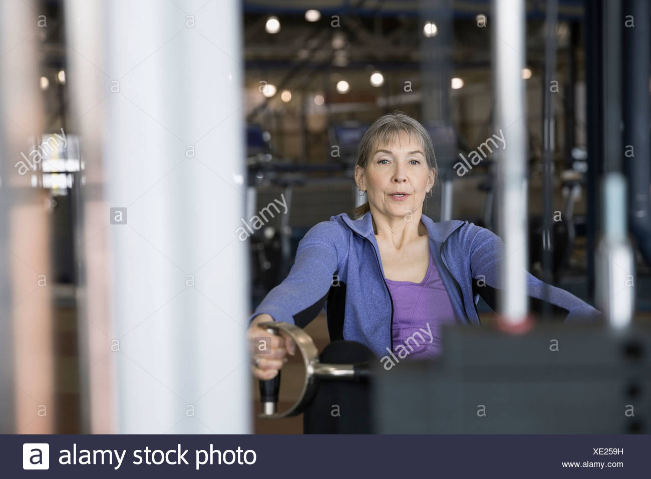 Woman using exercise machine at gym - Stock Image