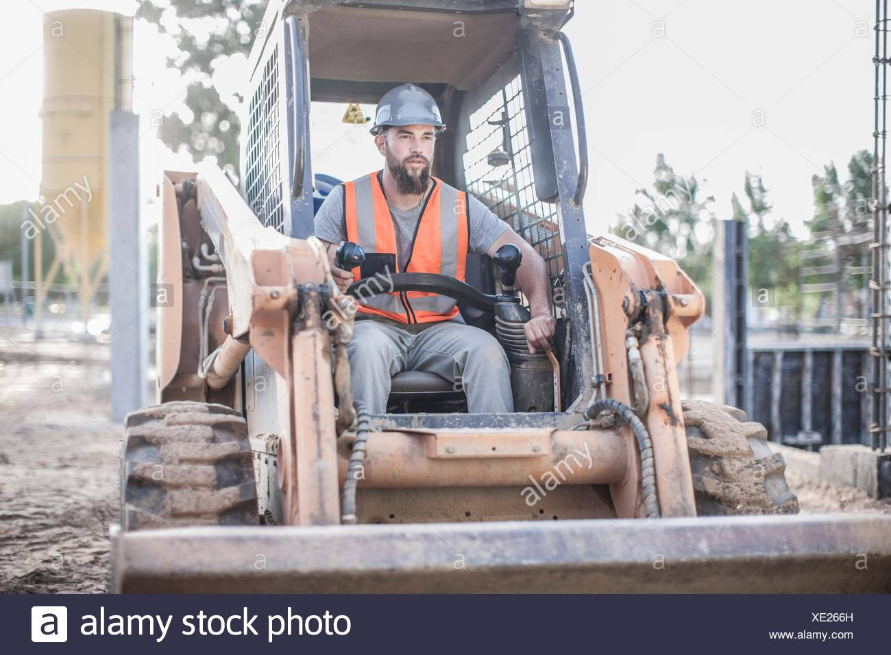 Builder driving excavator on construction site - Stock Image