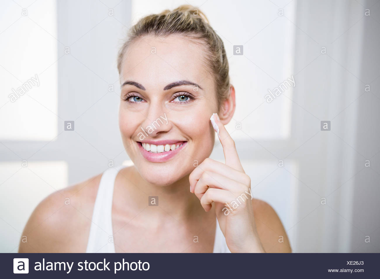 Young woman applying cream on face - Stock Image