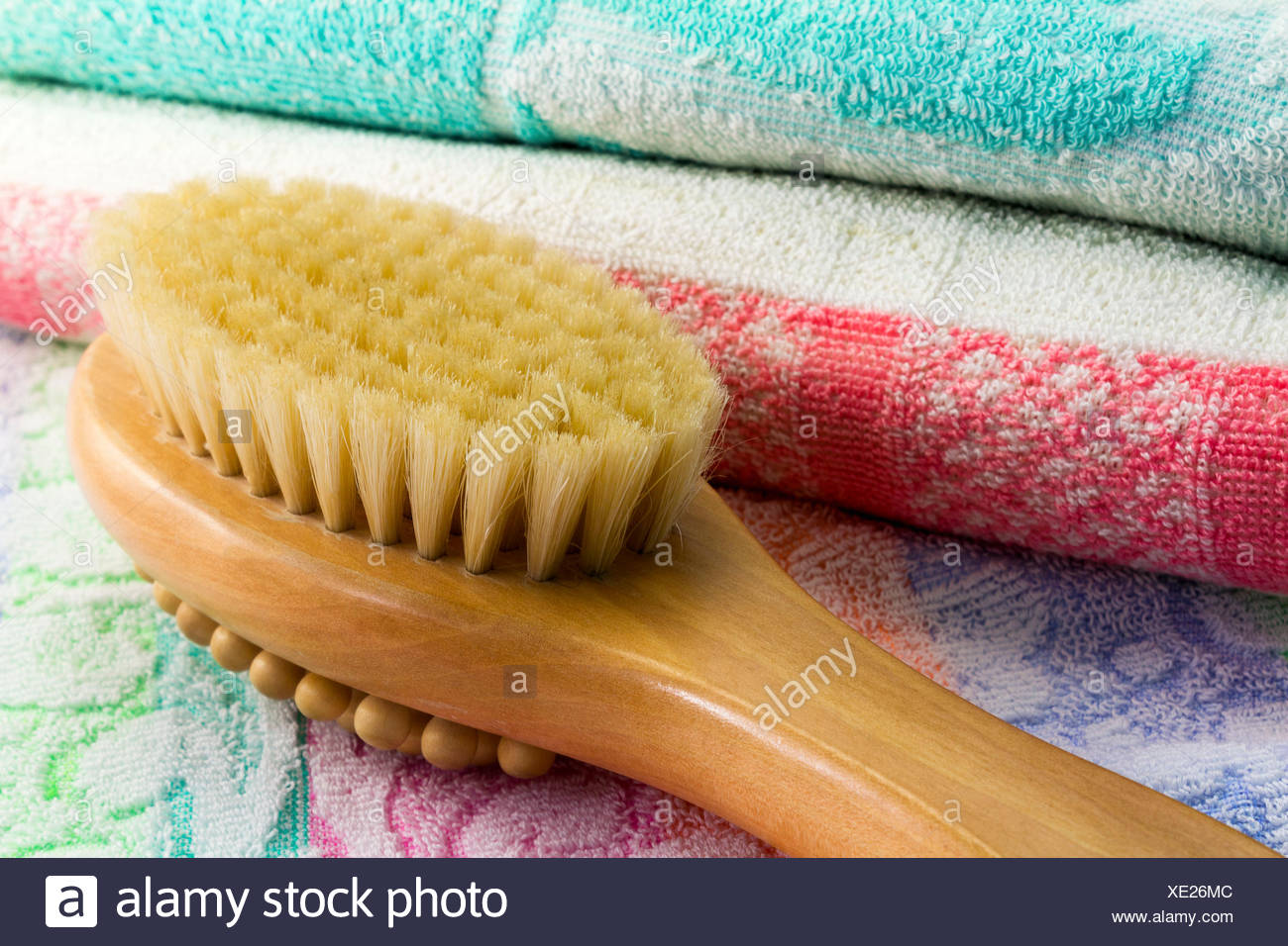 Wooden light brown brush with the long handle for body massage. Has wooden balls for massage and a rigid bristle for skin massage. Terry towel with an ornament. - Stock Image